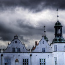 bright-white Ahrensburg castle in a thunderstorm in Germany